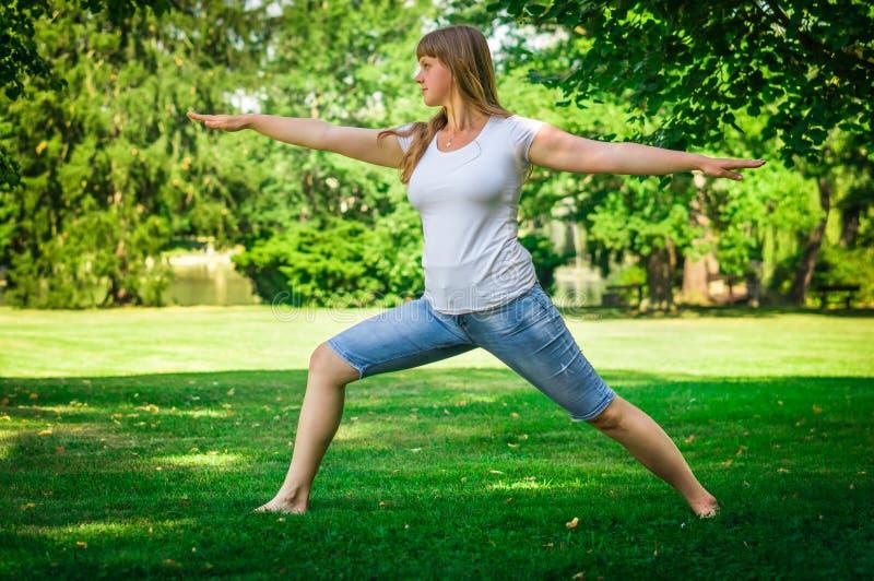 Giovane donna di forma fisica che allunga nel parco fotografie stock