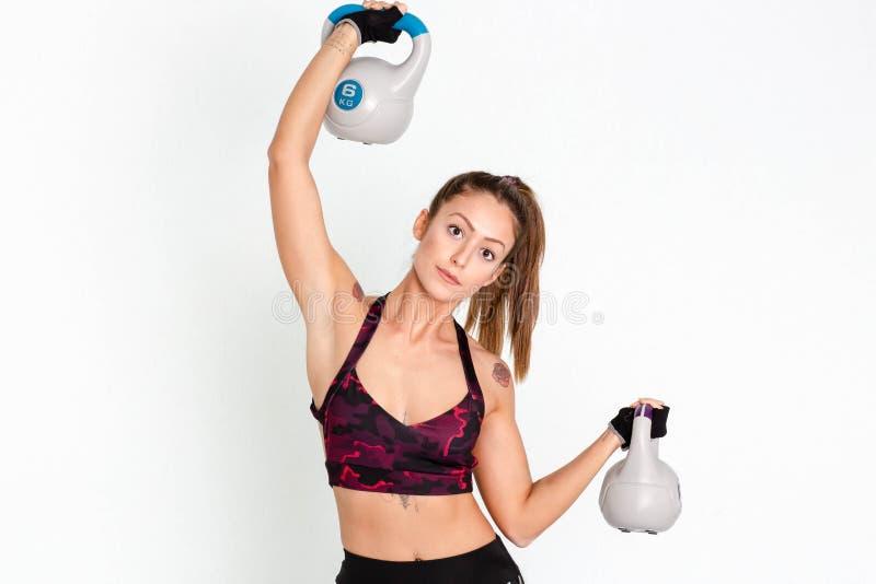 Giovane donna di forma fisica che oscilla i kettlebells durante l'addestramento del crossfit immagine fotografia stock libera da diritti