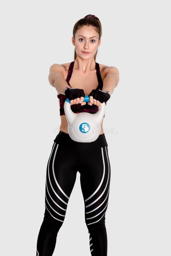 Giovane donna di forma fisica che oscilla il kettlebell durante l'addestramento del crossfit immagine immagini stock