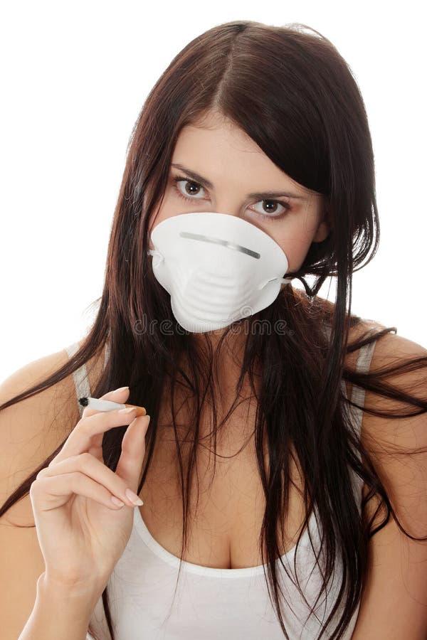 Giovane donna di fumo con la maschera di protezione immagine stock libera da diritti