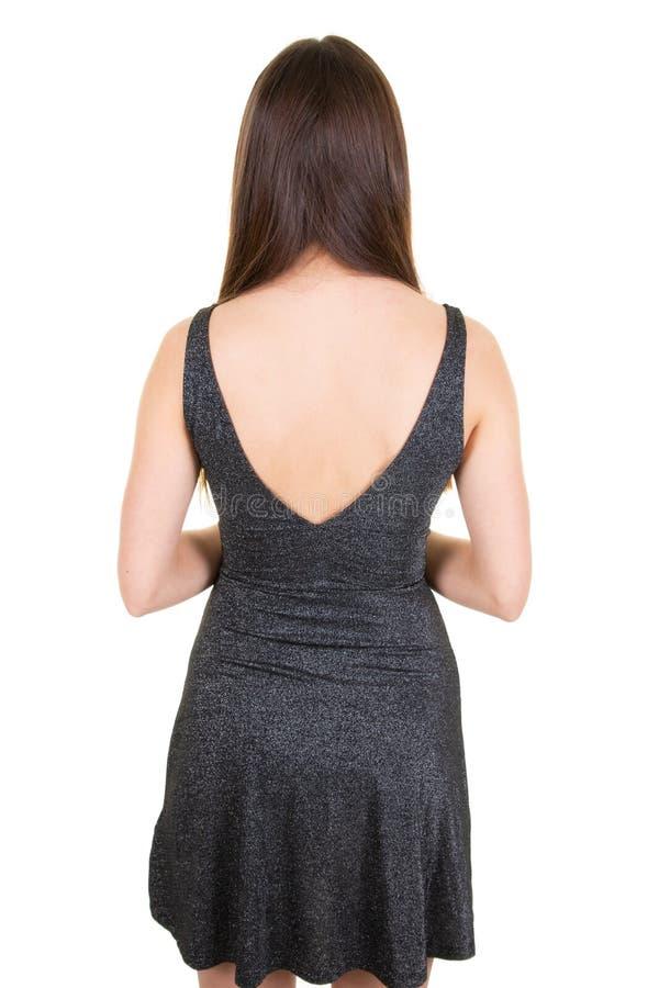 Giovane donna di misura che sta indietro con i capelli lunghi in vestito grigio su fondo isolato studio bianco fotografia stock libera da diritti