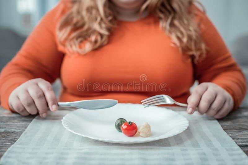 Giovane donna di peso eccessivo che mangia gli ortaggi freschi per la cena immagine stock libera da diritti