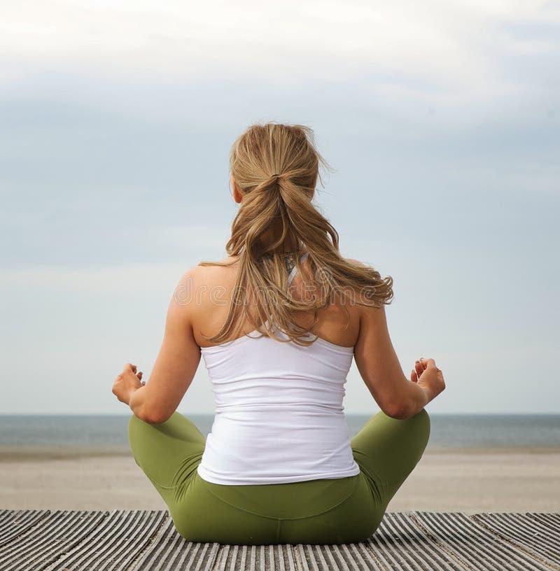 Giovane donna di retrovisione nella posa di yoga alla spiaggia fotografia stock libera da diritti