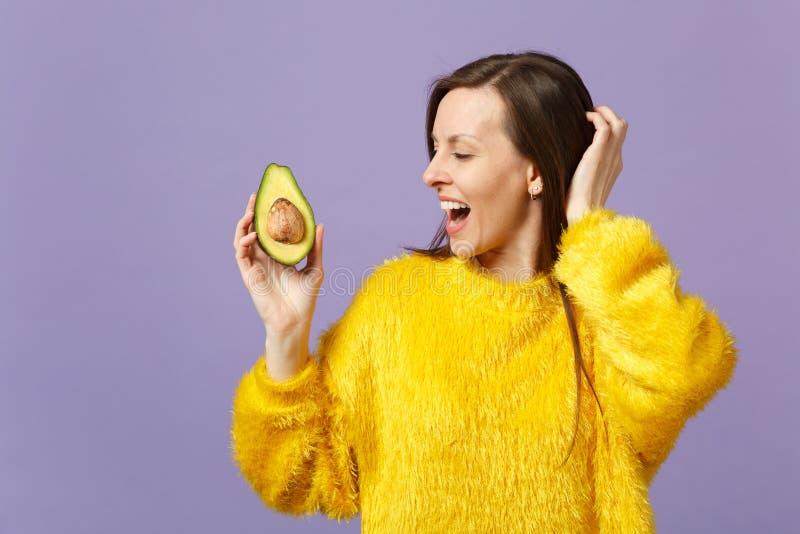 Giovane donna di risata allegra nella tenuta del maglione della pelliccia, considerante metà dell'avocado verde maturo fresco iso immagini stock libere da diritti