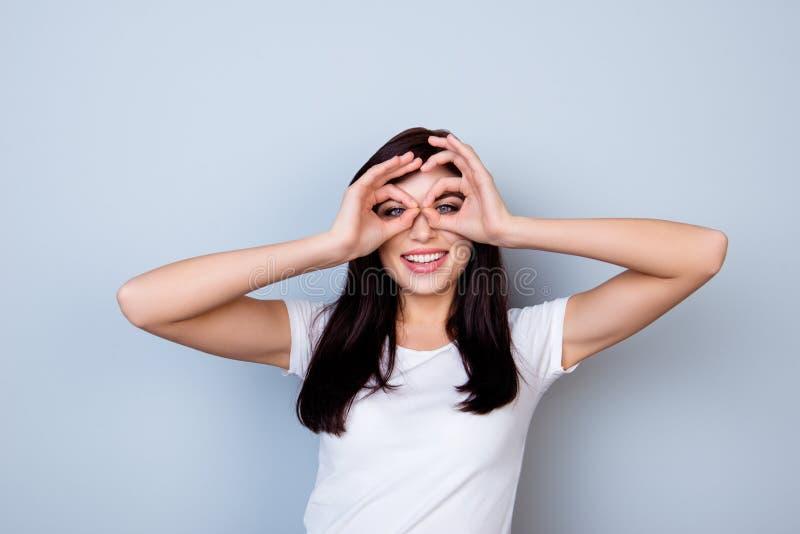 Giovane donna di risata attraente divertendosi e facendo il binocolo fotografia stock libera da diritti