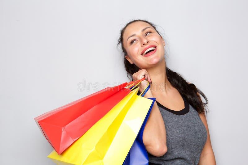 Giovane donna di risata che tiene le borse variopinte del regalo immagine stock libera da diritti