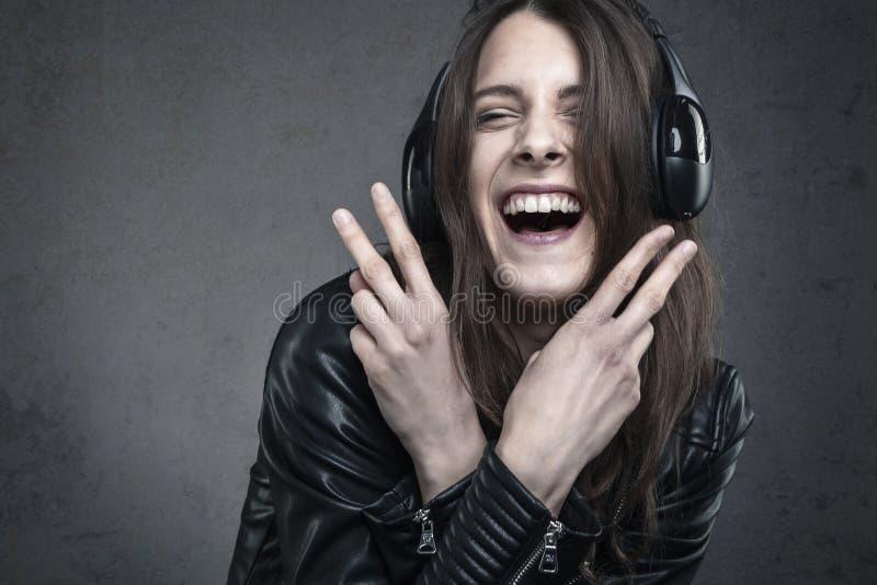 Giovane donna di risata con i telefoni capi che ascolta la musica contro immagine stock libera da diritti