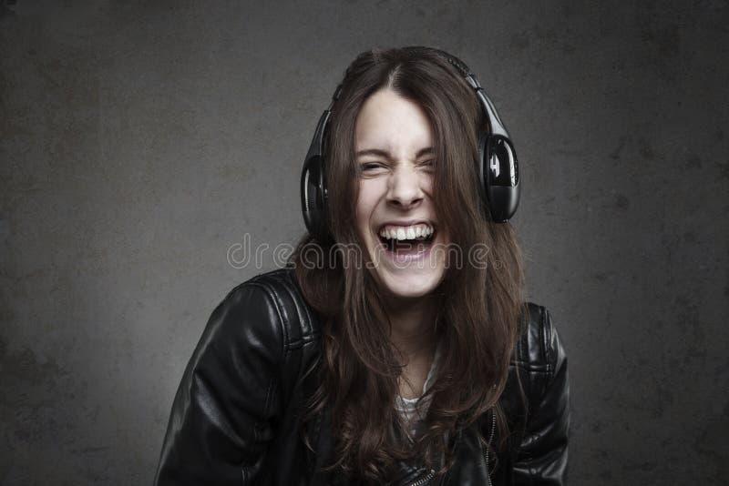 Giovane donna di risata con musica d'ascolto delle cuffie fotografie stock