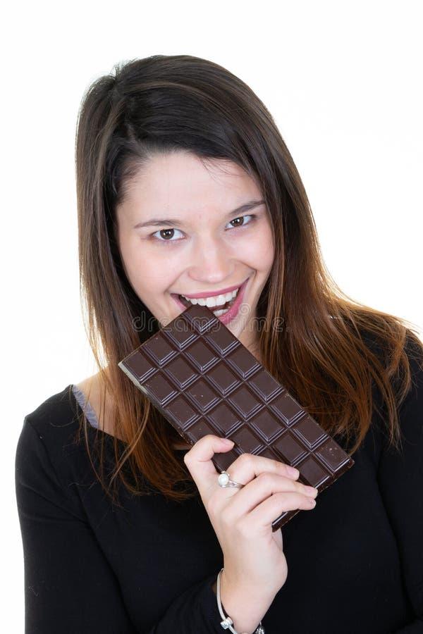 Giovane donna di risata in maglione nero che giudica a disposizione mordace e che mangia la barra di cioccolato isolata sul fondo fotografia stock