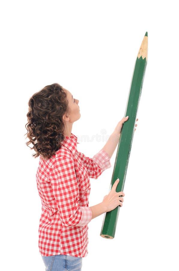 Giovane donna di scrittura con la grande matita verde fotografie stock