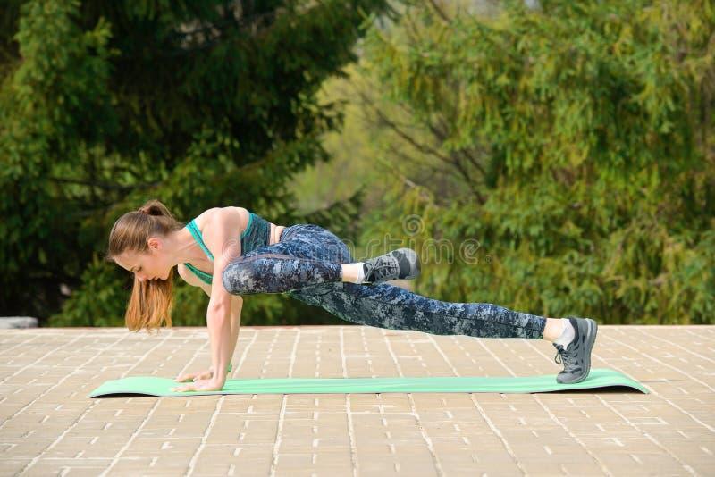 Giovane donna di sport in una tuta sportiva che fa esercizio della plancia durante l'allenamento in un parco della città immagine stock libera da diritti