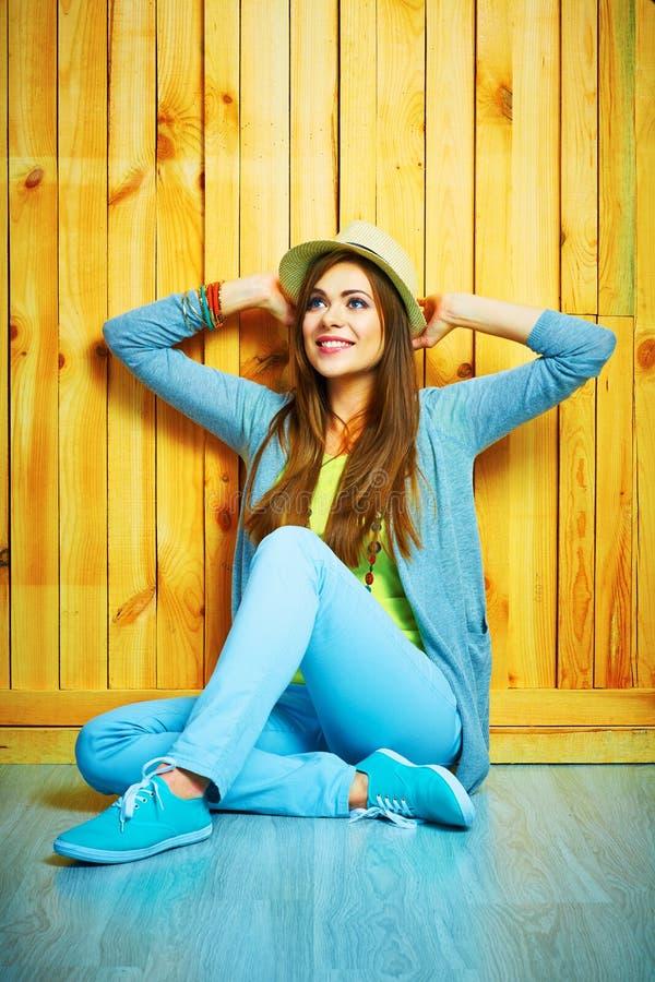 Giovane donna di stile dell'adolescente che si siede su un pavimento Sguardo in su fotografie stock libere da diritti