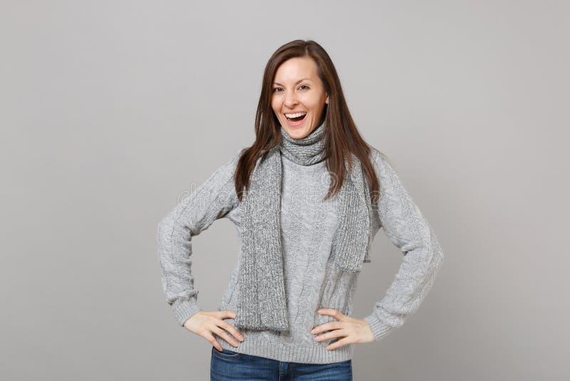 Giovane donna di stordimento in maglione grigio, condizione della sciarpa con le armi akimbo su fondo grigio in studio Sano fotografia stock libera da diritti