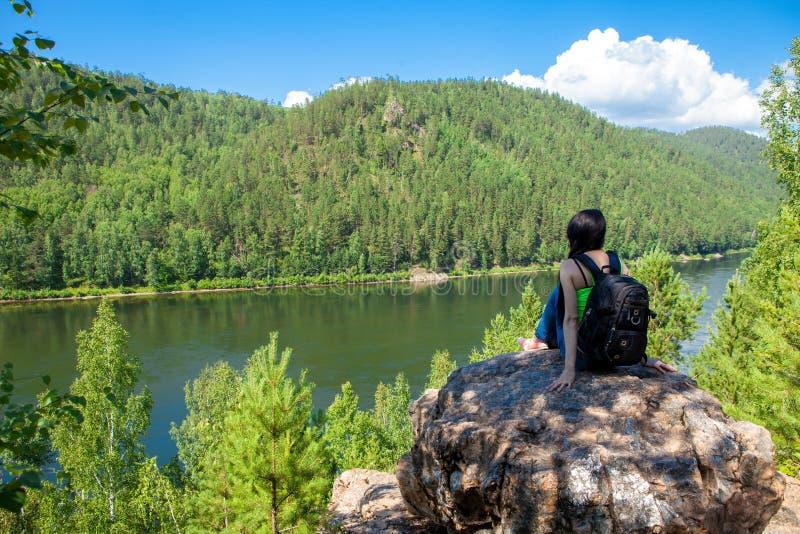 Giovane donna di viaggio che si siede sulla cima della scogliera della montagna fotografie stock