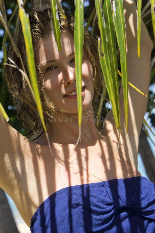 Giovane donna dietro una palma fotografie stock libere da diritti