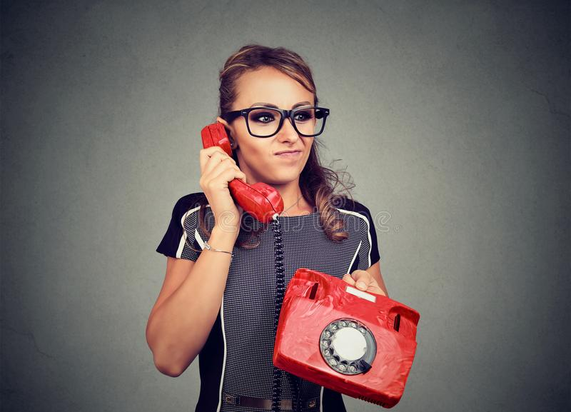Giovane donna dispiaciuta scontrosa che ha conversazione telefonica sgradevole immagini stock