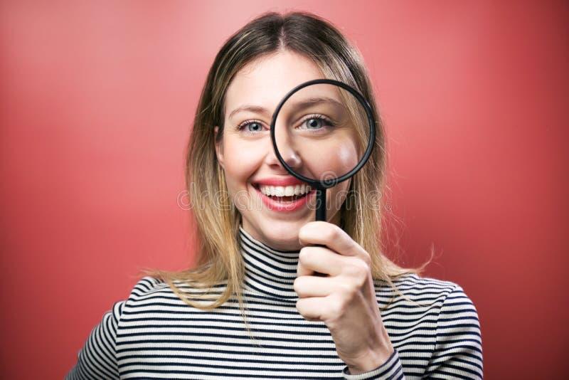 Giovane donna divertente che esamina tramite la lente d'ingrandimento la macchina fotografica sopra fondo rosa immagini stock
