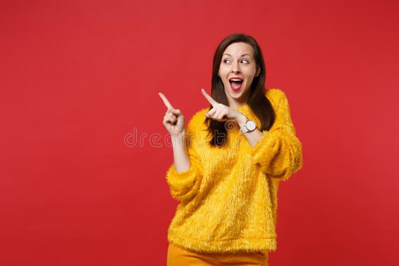 Giovane donna divertente in maglione giallo della pelliccia che tiene bocca aperta, guardando indicando i dito indice da parte is immagini stock libere da diritti