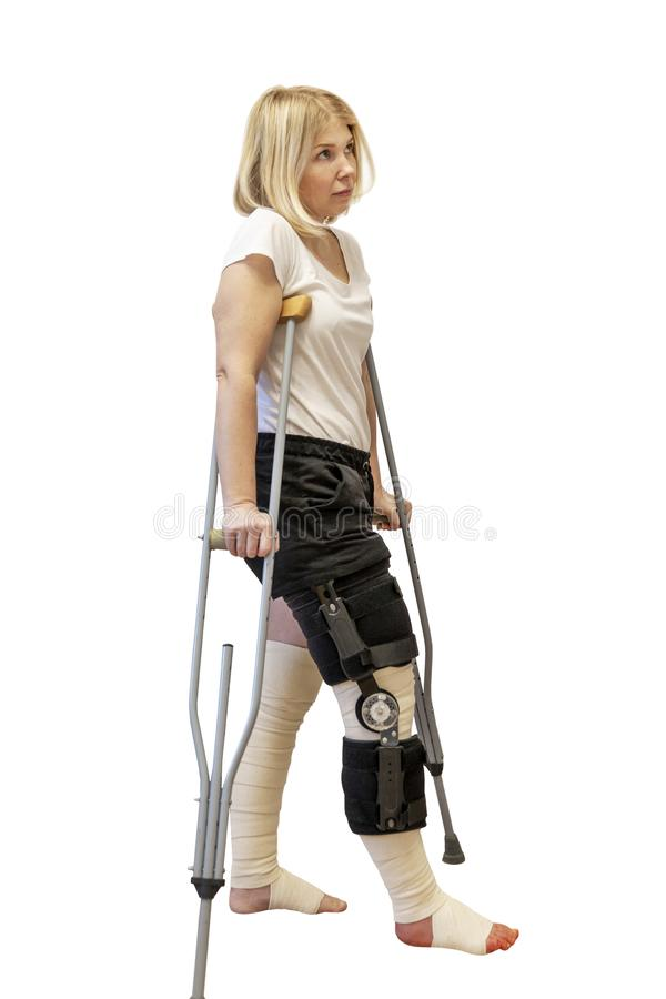 Giovane donna dopo la chirurgia del ginocchio Sulle grucce, in un'ortesi e con le gambe bendate Isolato su una priorit? bassa bia immagine stock libera da diritti