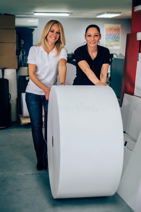 Giovane donna due che lavora nella fabbrica di stampa fotografie stock