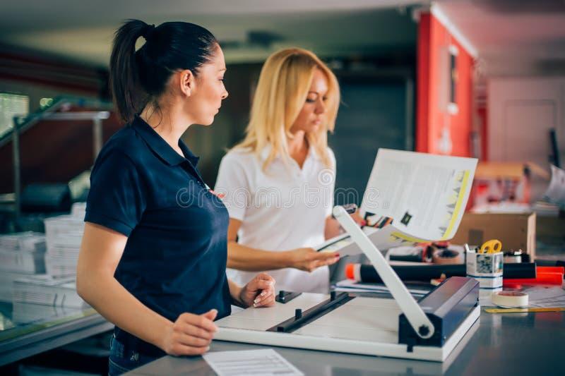 Giovane donna due che lavora nella fabbrica di stampa fotografia stock