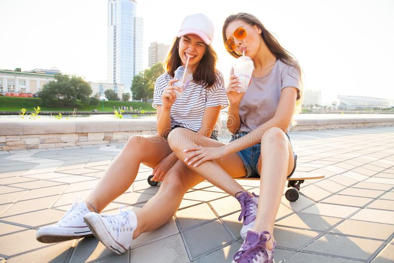 Giovane donna due che si siede sul sorridere felice del pattino Gli amici allegri godono del giorno soleggiato Urbano all'aperto  fotografie stock