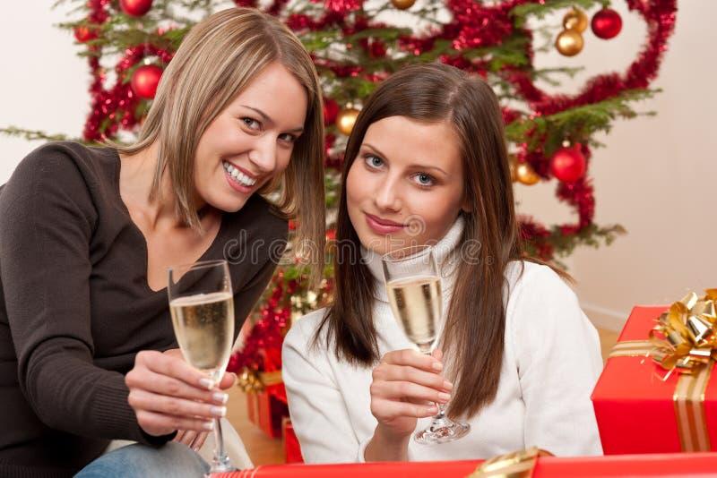 Giovane donna due con champagne e l'albero di Natale immagine stock