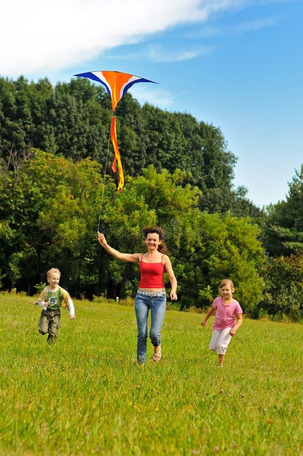 Giovane donna e bambini che pilotano un cervo volante fotografia stock