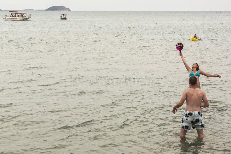 Giovane donna e giovane che giocano stare in acqua immagini stock