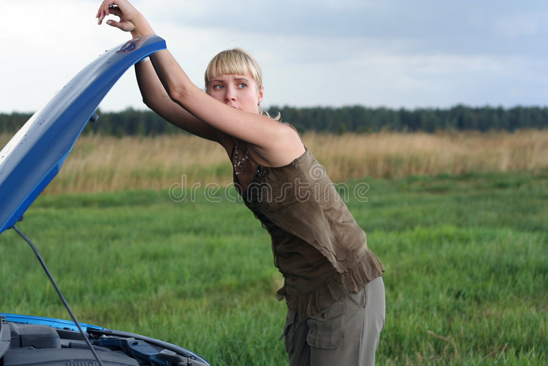 Giovane donna e la sua automobile rotta immagini stock libere da diritti