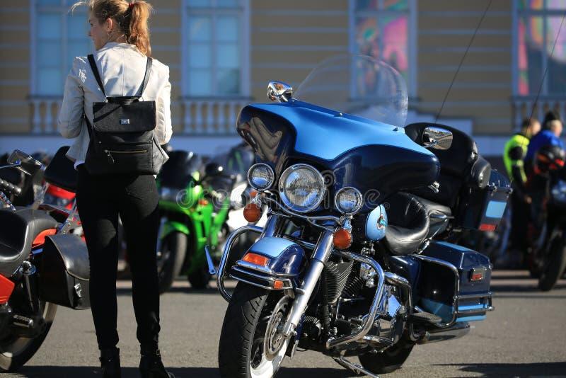 Giovane donna e motociclo blu parcheggiato di Harley-Davidson un giorno soleggiato immagini stock