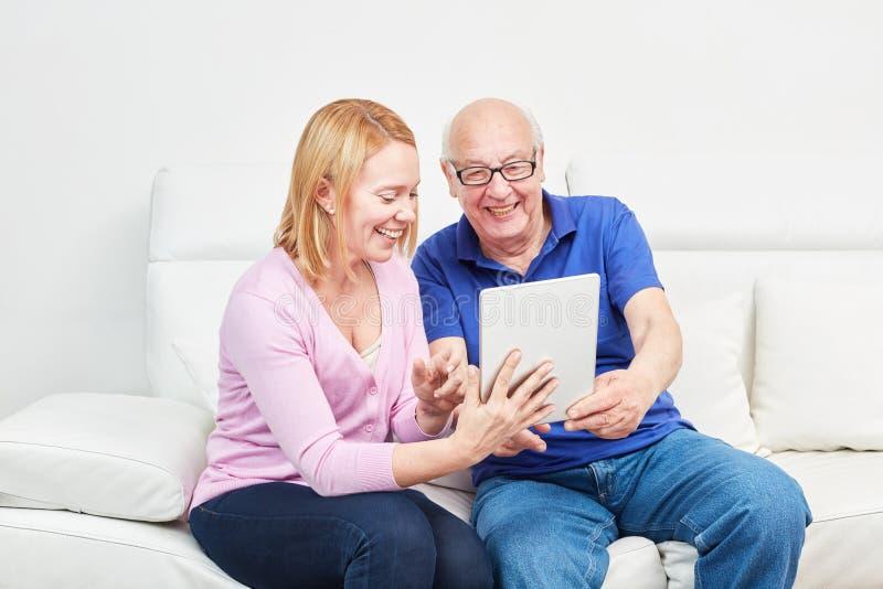 Giovane donna e senior con il computer portatile fotografia stock libera da diritti