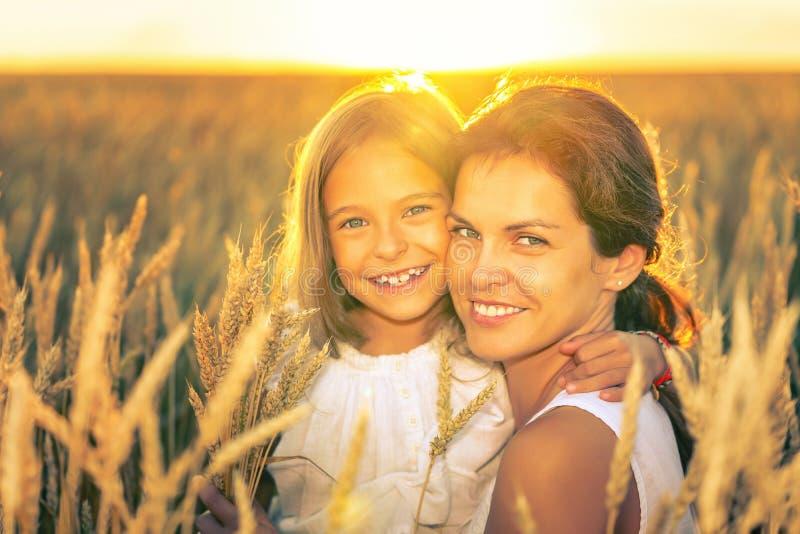 Giovane donna e sua figlia sul giacimento di grano dorato alla sera soleggiata fotografia stock