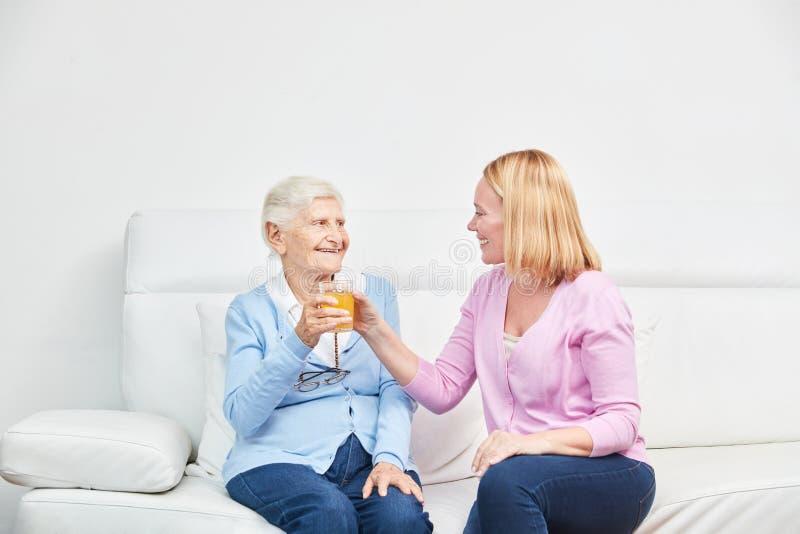 Giovane donna e succo senior della bevanda della donna insieme fotografie stock