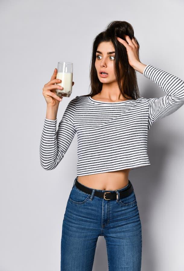 Giovane donna eccitata che tiene un bicchiere di latte, non sapendo se bere o non latte fotografia stock libera da diritti