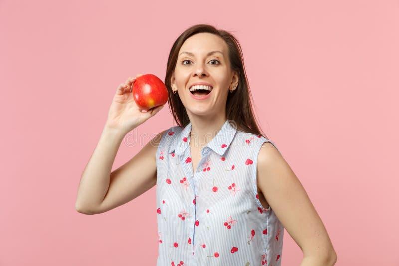 Giovane donna eccitata in vestiti di estate che giudicano la frutta rossa matura fresca della mela isolata sul fondo pastello ros fotografia stock libera da diritti
