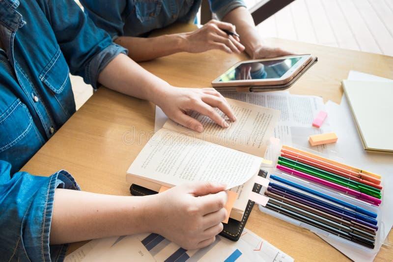 Giovane donna ed uomo che studiano per una prova un esame L'istitutore prenota i wi immagine stock libera da diritti