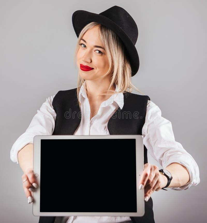 Giovane donna elegante alla moda in computer black hat della compressa della tenuta Schermo vuoto per il vostro testo o immagine fotografie stock libere da diritti