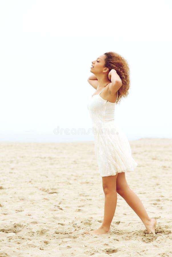 Giovane donna elegante che cammina sulla sabbia con le mani in capelli fotografie stock libere da diritti