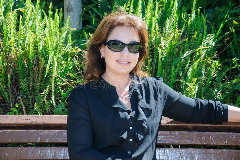 Giovane donna elegante che gode del sole nel parco fotografie stock