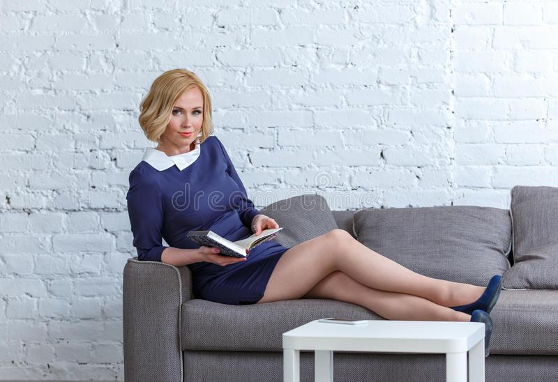 Giovane donna elegante che si trova su un sofà comodo con il suo diario fotografia stock libera da diritti
