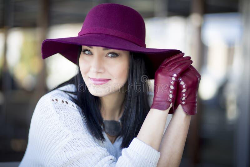 Giovane donna elegante con bello trucco nel cappello di Borgogna fotografia stock libera da diritti