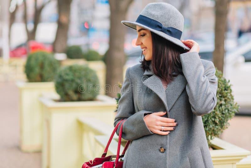 Giovane donna elegante del ritratto alla moda con capelli castana in cappotto e cappello grigi che cammina con la borsa sulla via immagine stock libera da diritti