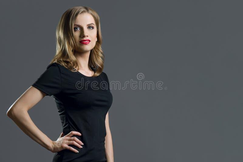 Giovane donna elegante di affari bionda in vestito nero Fondo grigio, copia-spazio immagini stock