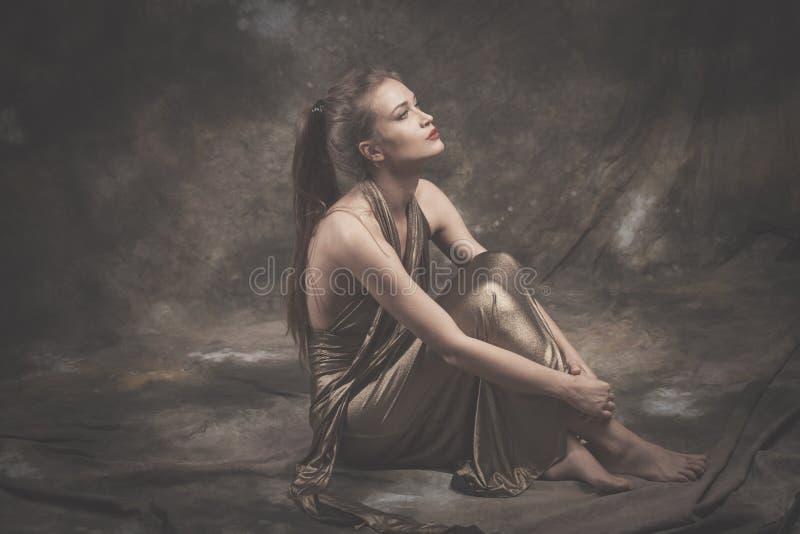Giovane donna elegante scalza in vestito dorato fotografie stock