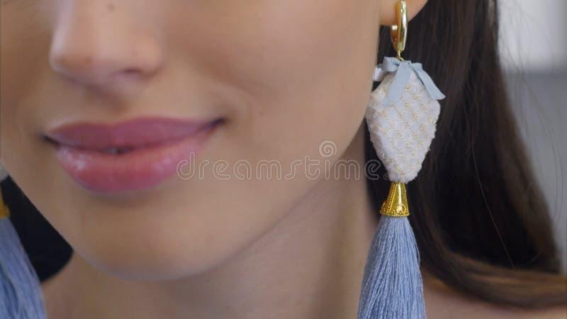 Giovane donna elegante sorridente che indossa gli orecchini lunghi che esaminano specchio e sorridere fotografia stock