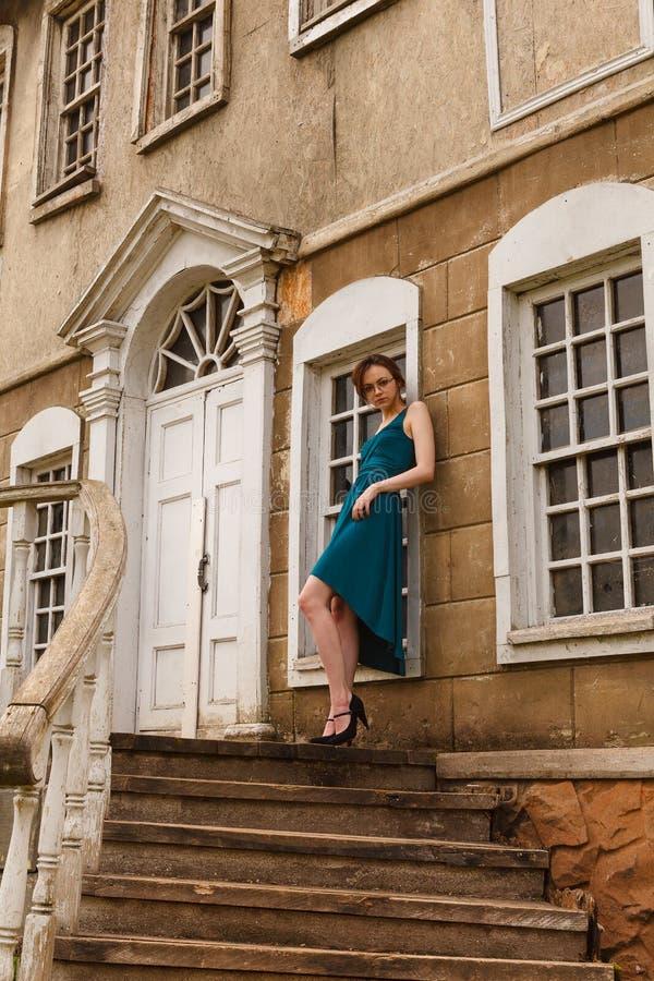 Giovane donna elegante sulla scala di vecchio palazzo immagini stock libere da diritti