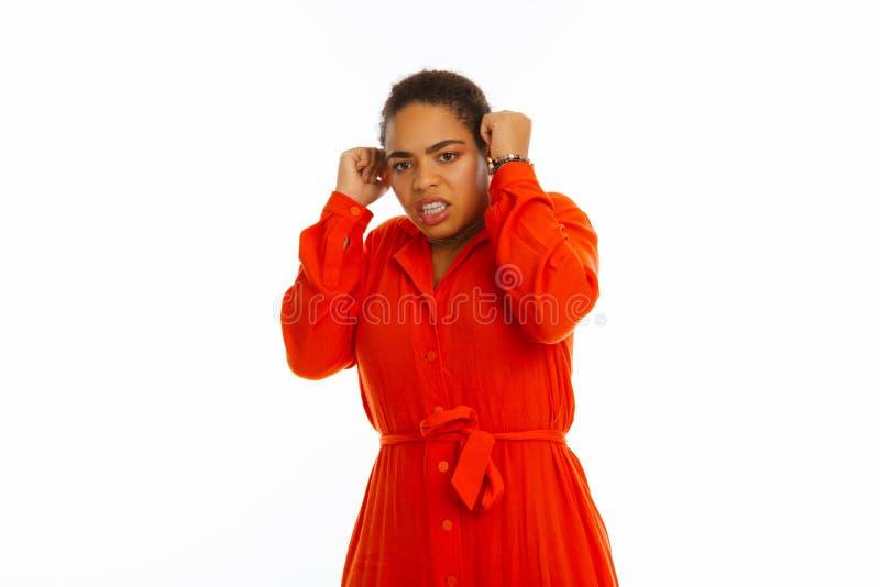 Giovane donna emozionale turbata che prova a coprire le sue orecchie fotografia stock libera da diritti