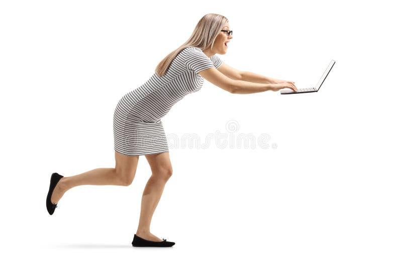 Giovane donna emozionante che corre e che scrive ad un computer portatile fotografia stock