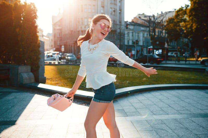 Giovane donna emozionante che indossa attrezzatura alla moda all'aperto Ragazza felice che salta e che si diverte Concetto di mod immagini stock
